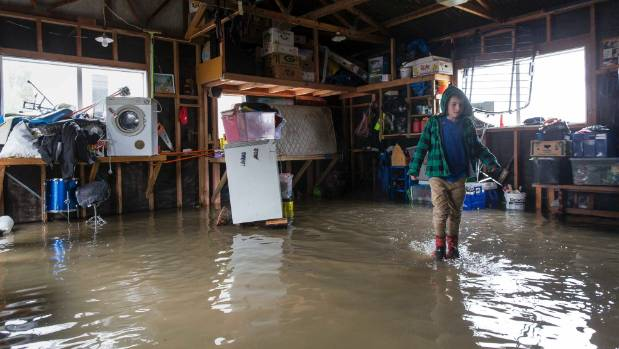 Leeston flooding. Selwyn St resident Joseph Gilmour, 9, wades through floodwater in his garage.