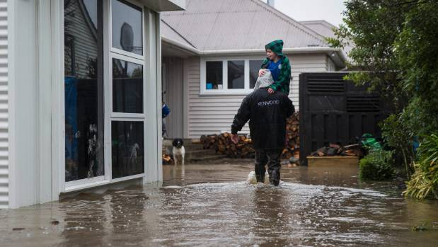 Leeston flooding. Selwyn St resident Joseph Gilmour, 9, is carried through the floodwater.