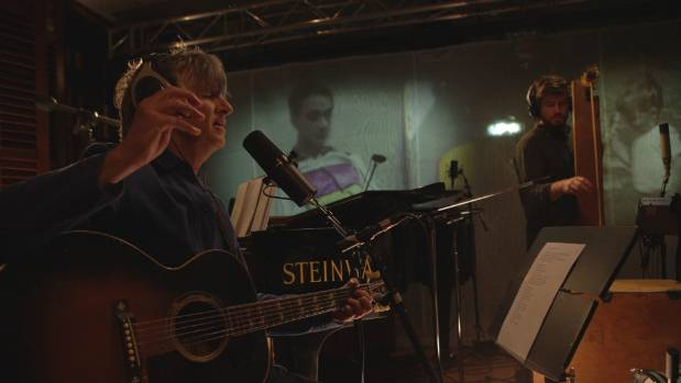 Neil Finn and his son Elroy play in the studio in front of an old home movie of Neil and his brother Tim.