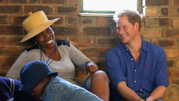 Prince Harry talks to a volunteer during a visit to a Mamohato Network Club for children living with HIV.