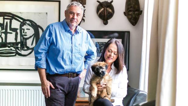 Derek West and Tracy Watkins with wheaten terrier, Murphy; on the walls are tribal masks bought by friend Simon Wilson ...