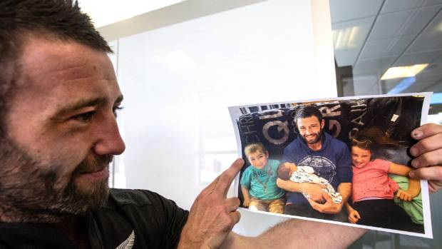 Jason Brokenshire looks at a recent photo of him with his three children.  He hopes to set up a support group for fellow ...