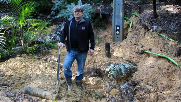 Charles Graves repairing a recent slip on his Onetangi property.