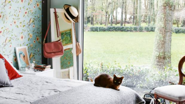 Grace's bedroom is a favourite haunt of Burmese cat Lara; Grace chose the English wallpaper patterned with flowers and ...