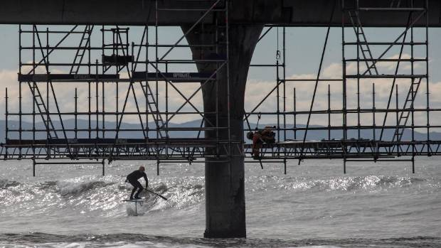 Pacific Paddle Board owner Sam Loader foils his Stand Up Paddle board near the scaffolding being used for the New ...