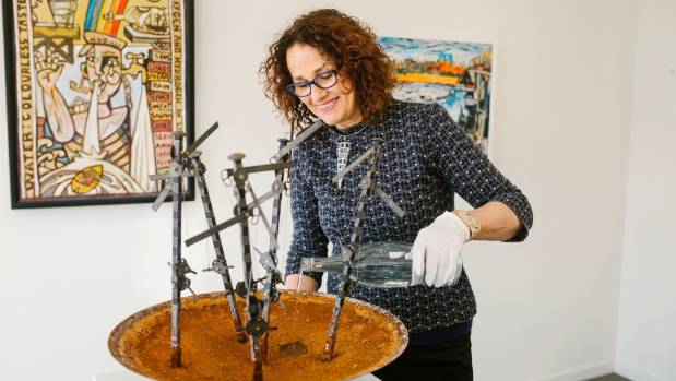 """Barbara Speedy pours water back into Graham Bennett's """"Pooling Ignorance"""" sculpture at The Diversion Gallery in Picton."""