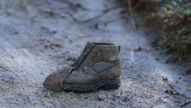 A lone, muddied boot could be seen by the edge of the road just inside the cordon.