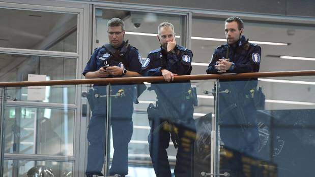 Armed Finnish policemen stand guard at the Helsinki airport, after stabbings in Turku.