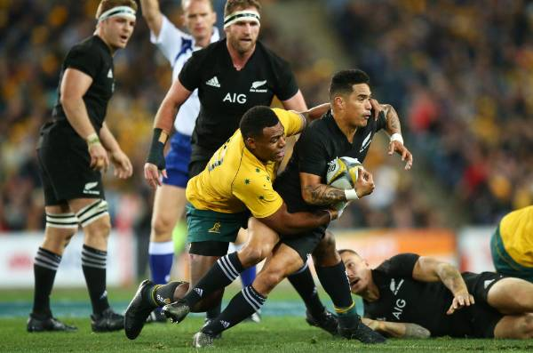 All Blacks halfback Aaron Smith is tackled.