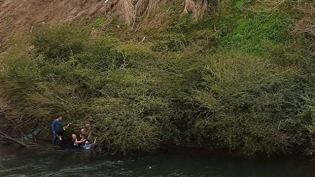 Rescuers work to free the couple from the ute shortly after it plunged 10 metres down the bank into the Waikato River at ...