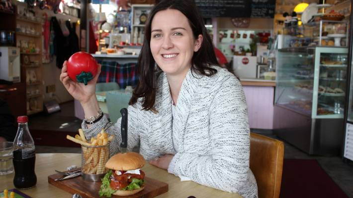 Turangi has a number of quirky stores and cafes, including Cadilac Cafe, where a customer prepares to chow down on their chicken burger