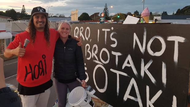 Otaki artist Hohepa Thompson, with Tracey Doyle, in front of a previous sign with which he courted controversy.