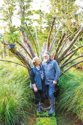 Carol and David beside the sculpture 'Queen of Wetland' which supports moss and lichen growths.