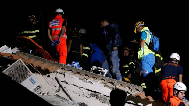 Rescue workers check a collapsed house after an earthquake hit the island of Ischia, off the coast of Naples, Italy on ...