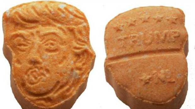 The front of each pill has Trump's coiffed hair and pursed lips. The back bears a resemblance to his campaign signs