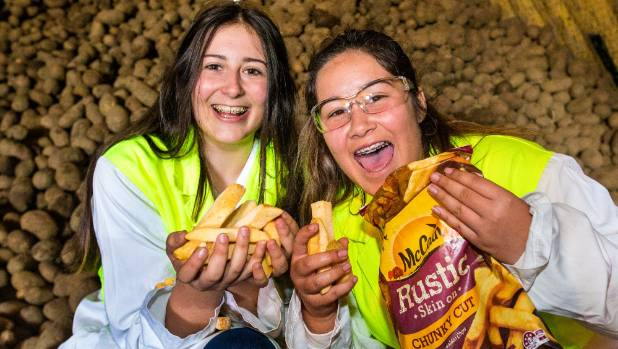 Students Summer Scott, 16, (left) and Ebony Keeley, 15, have fun in a McCain potato storage shed in Washdyke with some ...