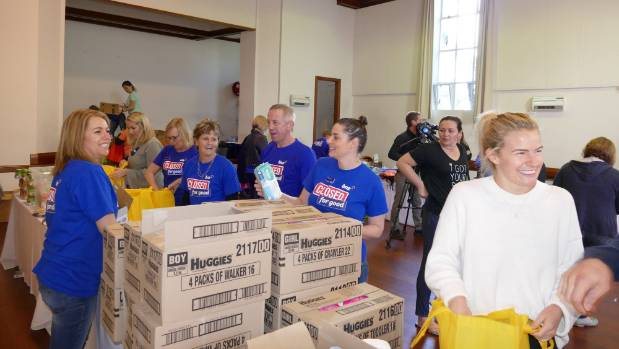 BNZ CEO, Anthony Healey (middle), BNZ volunteers and Matilda Rice help fill back packs for I Got Your Back Pack