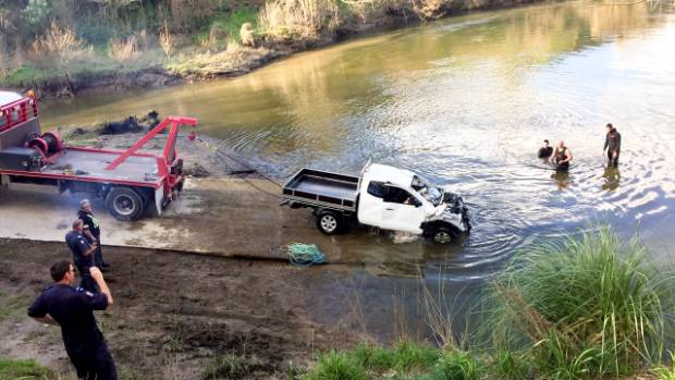 The Nissan Navara ute is pulled from the river after being floated by police divers.