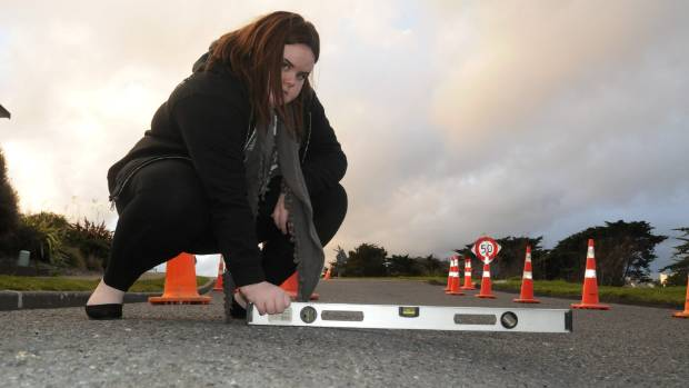 Sarah King, 14, uses a spirit level to show how uneven the road has become.