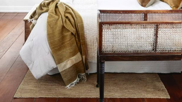 In a bedroom, place a large rug underneath the bed with a generous amount visible at the foot and sides. Keep bedside ...
