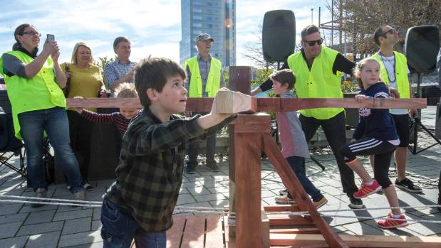 Children help raise the wooden steeple in Cathedral Square on Sunday.