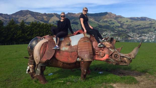 Olivia Watkins, left, and Maddison Northcott on the rhino sculpture at the peak of the Children's Bay walkway on Banks ...