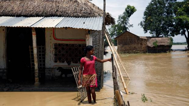 A girl stands in front of a house at the flood affected area in Saptari District, Nepal.