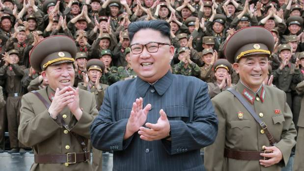 North Korean leader Kim Jong Un was present at a factory as the nuclear weapon was loaded on to a missile, state media says.