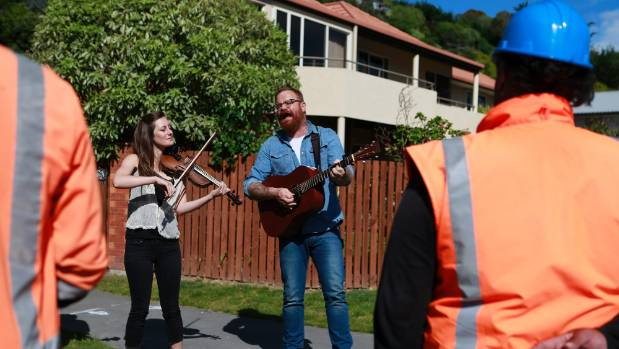 Sonny Makiri, right, a traffic controller for SCIRT, watches Adam McGrath, on guitar, and Alice Ryan-Williams, on ...