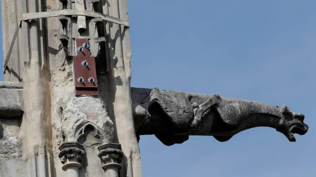 A gargoyle and part of a damaged pinnacle at the Notre Dame Cathedral in Paris.