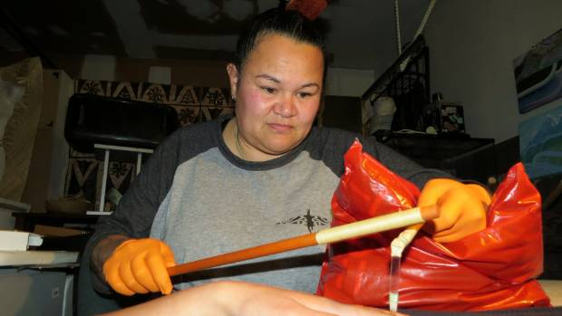 Chris Harvey using uhi, traditional tattoo tools.