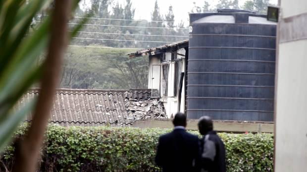 Investigators look at the burnt dormitory.