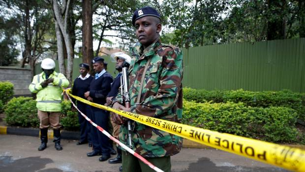 Policemen stand in front of a cordon at Moi Girls school in Nairobi after the fire.