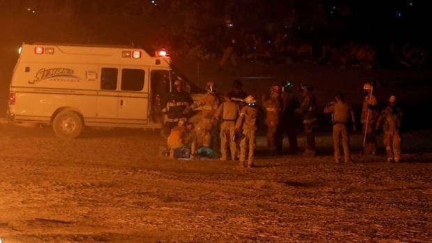 Emergency personnel help the man after pulling him from the fire.