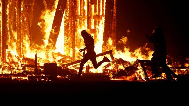 """A Burning Man participant evades a firefighter and runs into the flames of the """"Man Burn""""."""