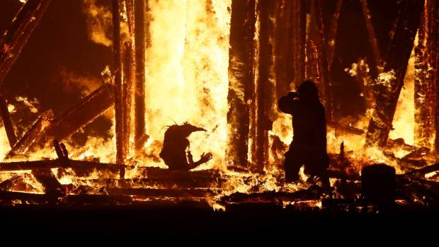 A firefighter wades into the flames to try to reach the man.