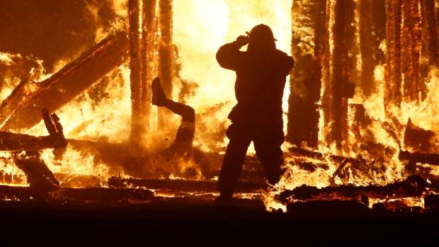 A firefighter watches as a Burning Man participant runs straight into the inferno.