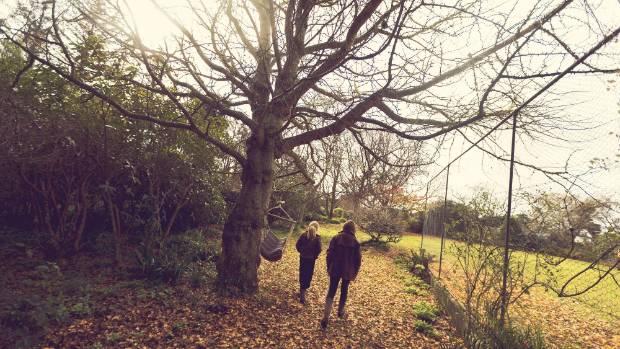 Ava and Carly Thomas walk through their Kiwitea garden.
