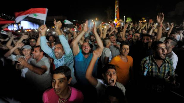 Syrians gathered in a square in Damascus to watch their national football team on a big screen celebrate the 2-2 draw ...