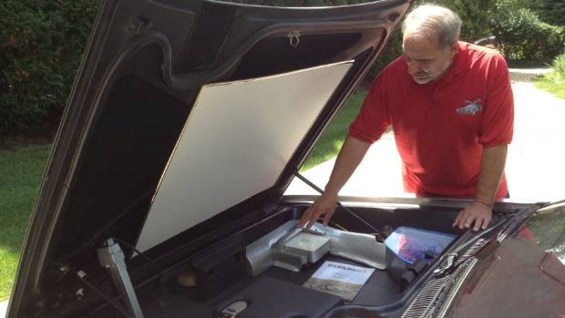 Bob Brandys of Hinsdale shows the Apple Mac mini computer his son installed in his DeLorean to connect to the Internet.
