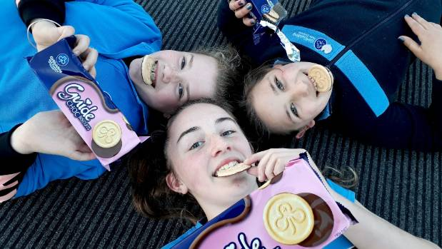 Emilia Brown, 10, Lydia Blomfield, 12, and Ava Wairau, 9, of the Waikiwi Guide unit, enjoy some Girl Guide biscuits.