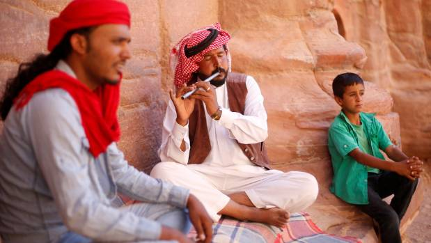 Local resident Ahmed Hunaiti (C), plays the flute as he waits for tourists to buy souvenirs.