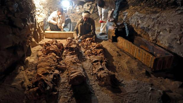 Egyptian antiquities workers preserve mummies in the recently discovered tomb.