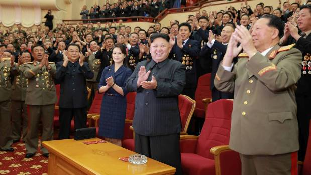North Korean leader Kim Jong Un claps during a celebration for nuclear scientists and engineers who contributed to