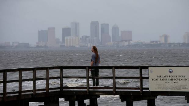 The Tampa skyline is seen in the background as a man looks out at Hillsborough Bay ahead of the arrival of Hurricane