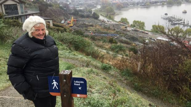 Wanaka resident Judy Cook takes in a view of the Lakeside Road landslip during snowy conditions on Saturday.