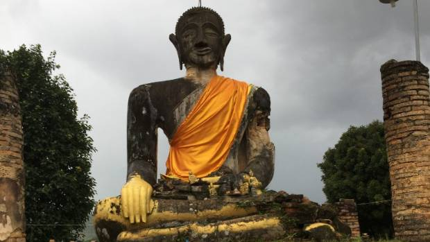 The giant sitting Buddha presiding over the ruins of his temple at Wat Phia Wat in Muang Khoun.