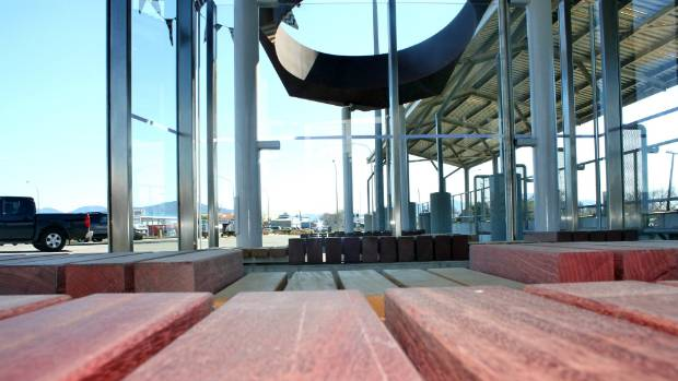 The bus shelter features indoor and outdoor areas with wooden seats and glass walls.