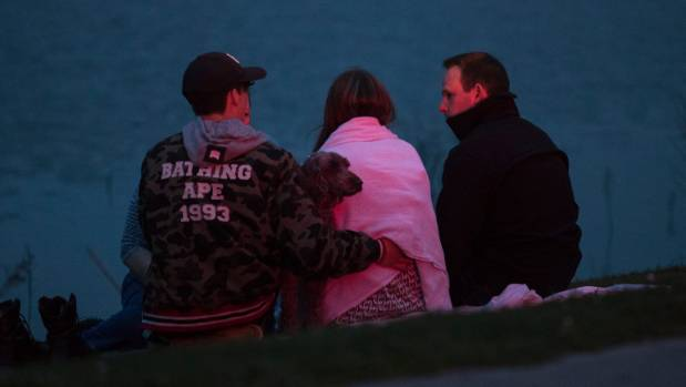 A woman is comforted after attempting to rescue a couple who disappeared into a lake at the Westlake Reserve in Halswell.