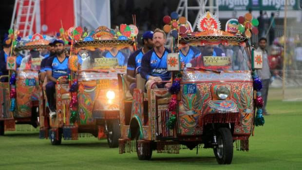 The World XI players arrive on the pitch in rickshaws at Ghaddafi Stadium